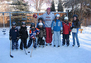 Image of Wayne with children on homemade rink.
